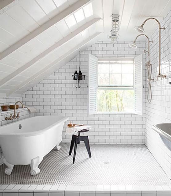 un arioso bagno bianco con piastrelle della metropolitana e penny e stucco nero, una vasca con i piedini e uno sgabello nero