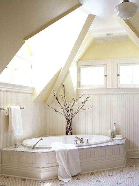 un bagno cremoso con lucernari, una vasca da bagno incorporata e una disposizione dei rami in un vaso
