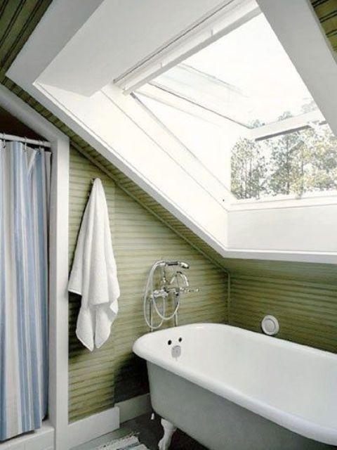 un bagno in mansarda verde con un tocco vintage, una vasca con i piedini e uno spazio doccia con una tenda a righe