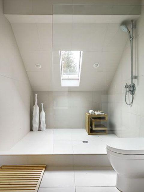 un piccolo bagno mansardato contemporaneo con piastrelle color crema di grandi dimensioni e un lucernario nella doccia