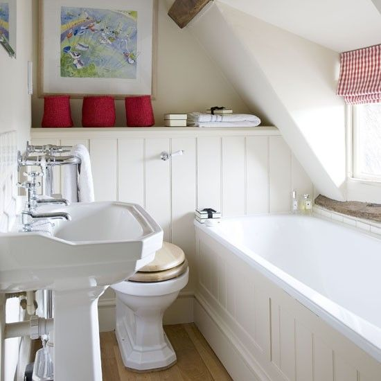 un piccolo bagno in mansarda cremoso fatto con perline, un lavandino indipendente e tocchi di rosso