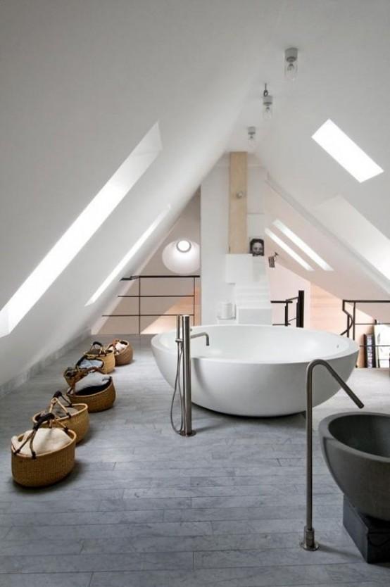 un bagno mansardato contemporaneo con un pavimento di piastrelle grigie, una grande vasca rotonda e alcuni cestini per la conservazione