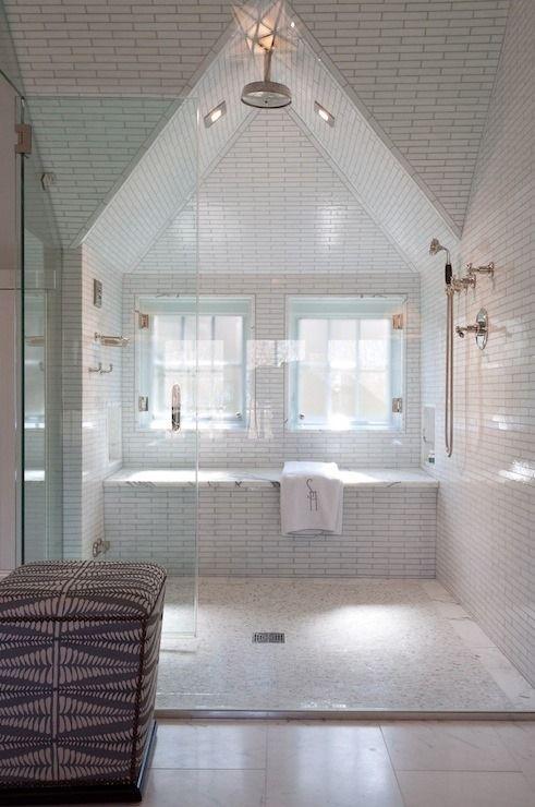 un bagno mansardato neutro con piastrelle bianche evidenziate con stucco nero, infissi metallici e un grande pouf imbottito