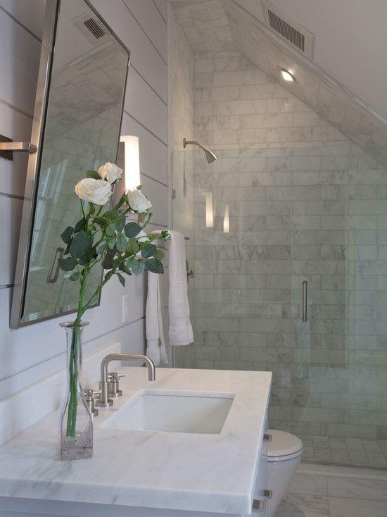 un piccolo bagno in mansarda mansardato in marmo con un lavandino quadrato in marmo e un piccolo spazio doccia