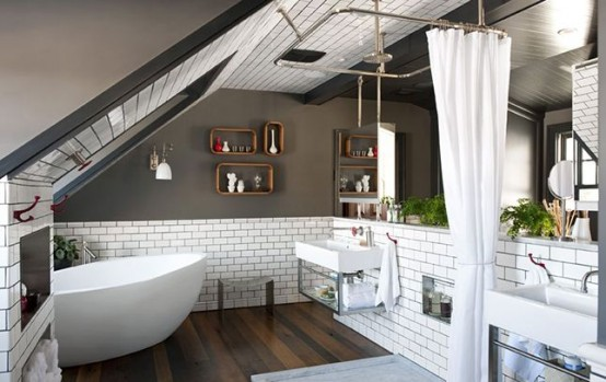 un bagno in mansarda di ispirazione industriale con pareti grigie, piastrelle bianche della metropolitana, una vasca ovale, uno spazio doccia e due lavandini