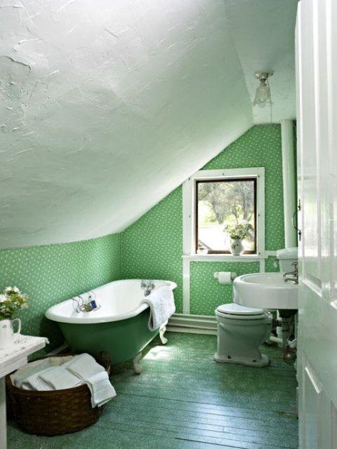 un bagno in mansarda grene fatto con carta da parati, un muro verde e una vasca con piedini verdi plsu un cestino per la conservazione