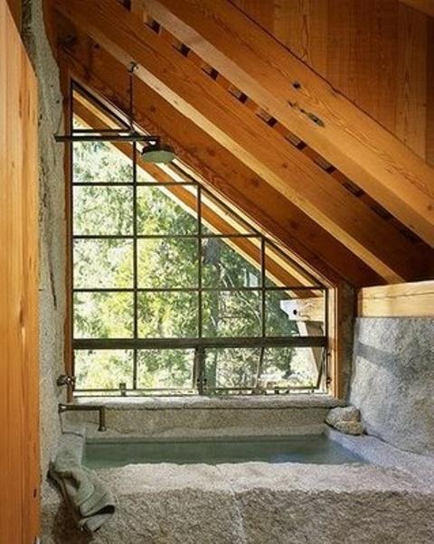 un bagno in mansarda in pietra e legno con vasca per il relax e soffitto in legno