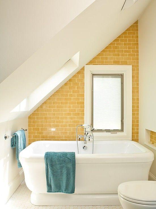 un luminoso bagno in mansarda con un muro giallo, una grande vasca e asciugamani blu
