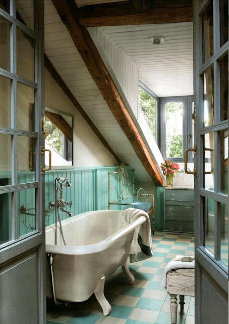 un colorato bagno mansardato fatto con travi in legno, tocchi turchesi e una vasca vintage