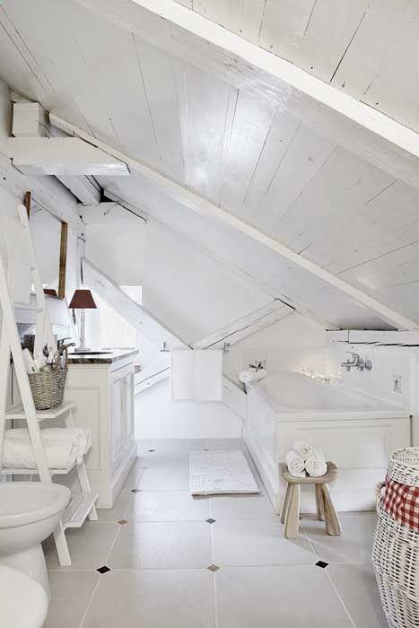 un bagno in mansarda bianco puro con un tocco vintage, legno imbiancato, una vasca, una scala per riporre e un lavandino in bianco