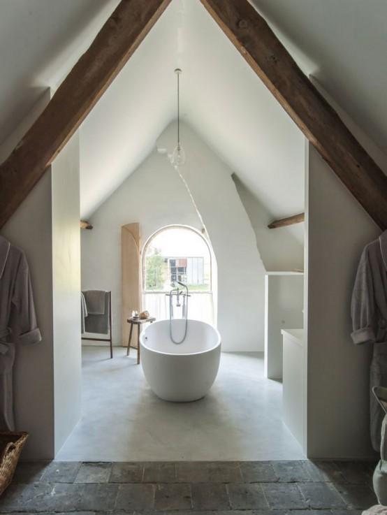 un bagno in mansarda neutro con ampia finestra ad arco, una vasca e alcuni mobili per ripostiglio