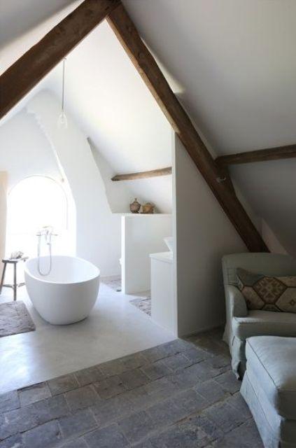 un piccolo bagno in mansarda bianco con travi in legno, una vasca ed alcuni ripiani per riporre gli oggetti