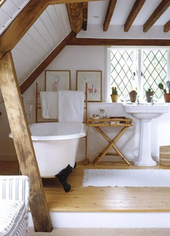 un bagno rustico mansardato con travi in legno, vasca con piedini, lavabo free-standing e mobili in legno