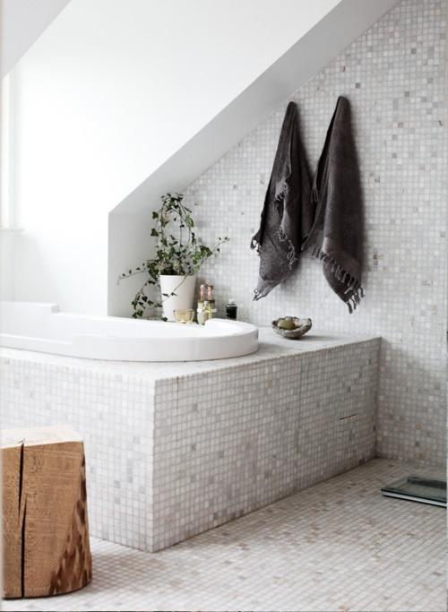 un bagno in mansarda neutro con una vasca incassata, piastrelle di piccole dimensioni e un tavolino da tronco d'albero