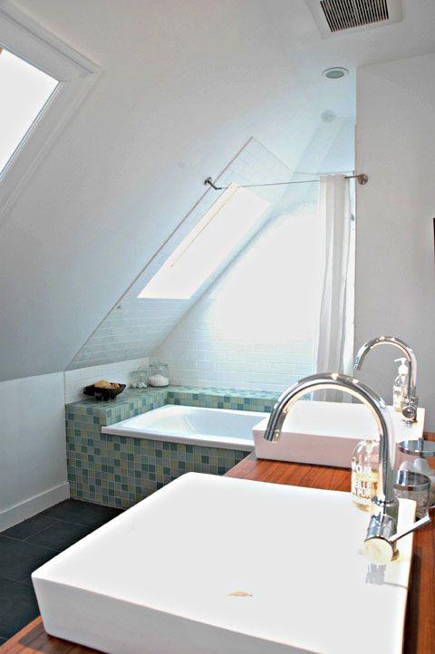 un piccolo bagno in mansarda con vasca rivestita in piastrelle blu, doppio lavabo in legno, lucernari