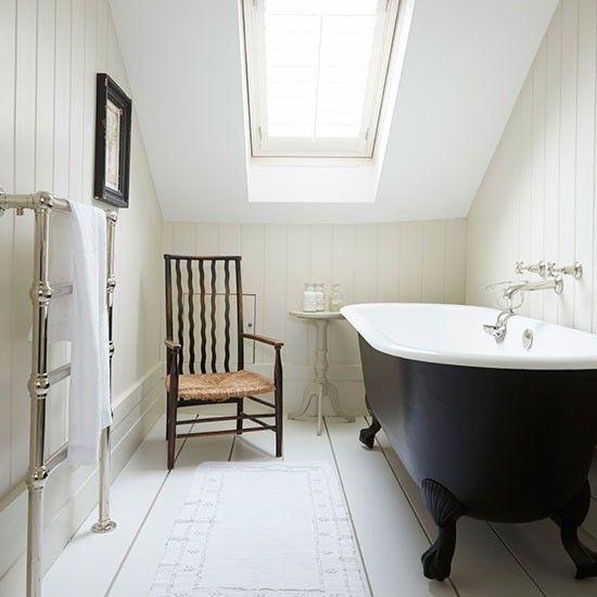 un bagno in mansarda vintage neutro con un lucernario e una vasca con piedini neri, una sedia vintage