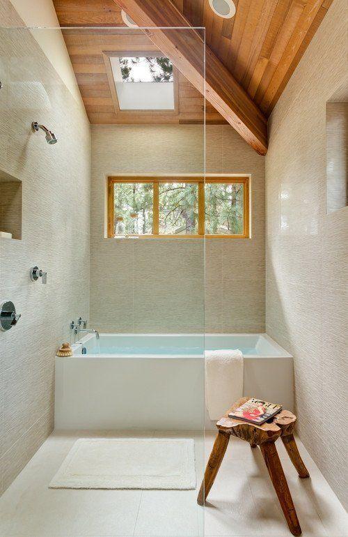 un bagno neutro con piastrelle materiche, un soffitto in legno e uno sgabello, uno spazio doccia