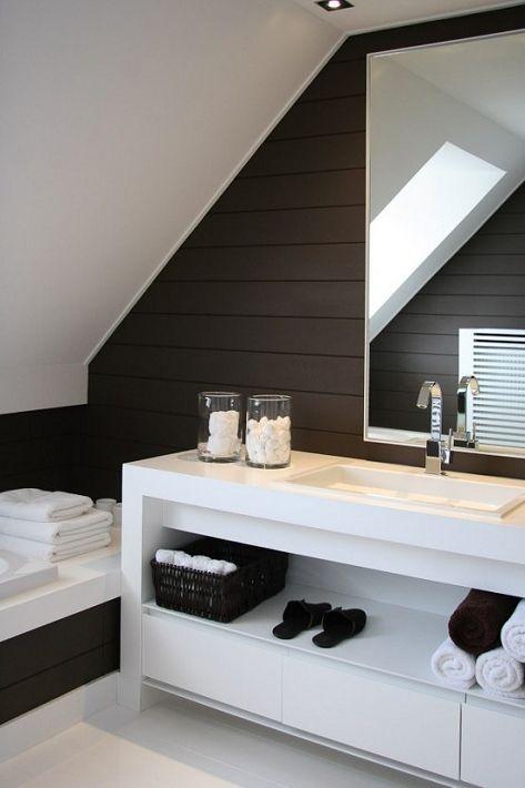 un bagno minimalista a contrasto in marrone scuro e bianco, con una grande vanità bianca e asciugamani bianchi