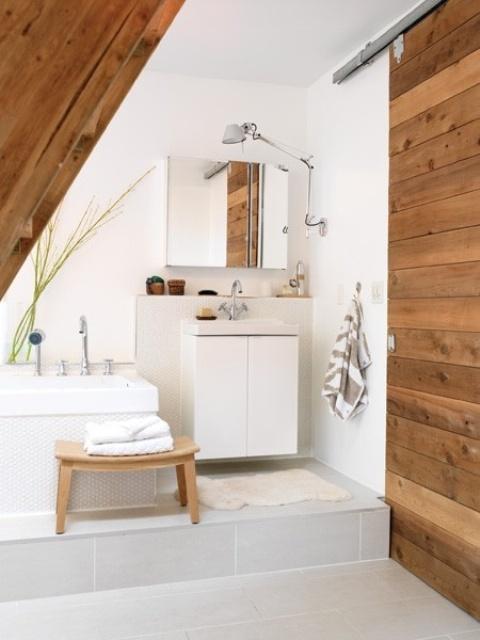un bagno neutrla con tocchi e mobili in legno, una vasca geometrica e vanità