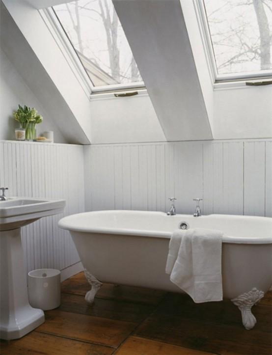 un bagno in mansarda bianco con lucernari, un lavandino autoportante e una vasca con piedini