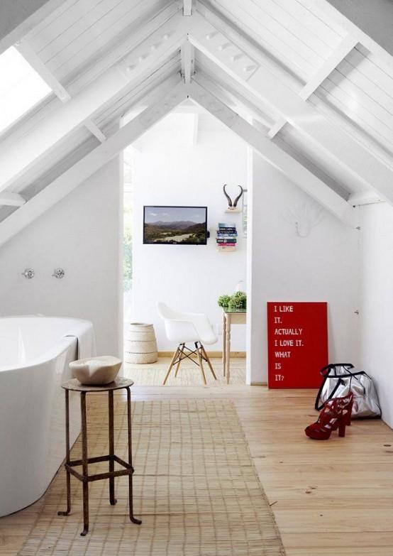 un bagno in mansarda bianco con vasca ovale, alcuni mobili e un tappeto di iuta, lo spazio è inondato di luce
