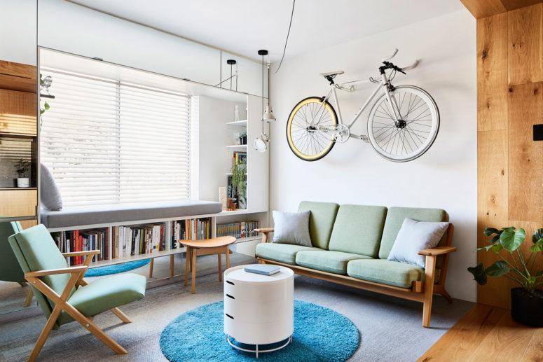 Il soggiorno è dotato di comodi mobili contemporanei, un posto vicino al finestrino con una libreria e una bicicletta sul muro