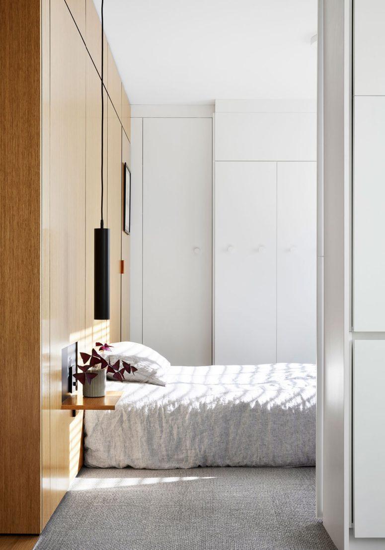 La camera da letto è piccola e laconica, presenta una testiera in legno che funge da contenitore, comodini galleggianti e lampade a sospensione