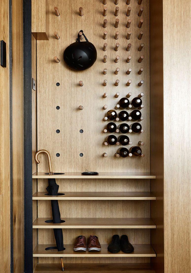 L'ingresso è confortevole e minimalista, con legno chiaro e ripiani eleganti
