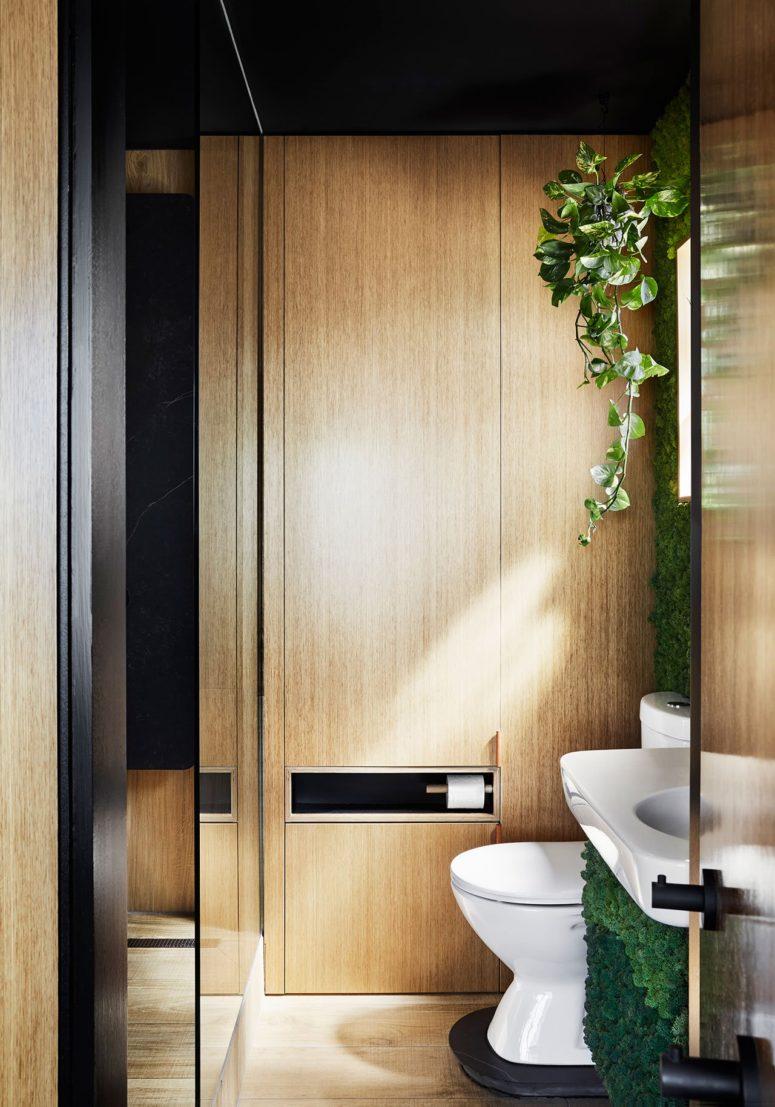 Il bagno è dotato di doccia e molto legno chiaro e superfici nere per continuare la combinazione di colori dell'appartamento