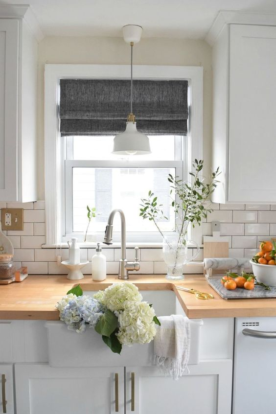 le tonalità di grigio romano aggiungono un tocco di colore alla cucina completamente bianca e la mantengono privata quando necessario