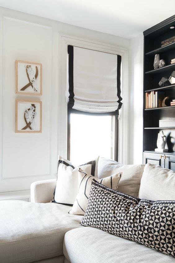 le tonalità romane bianche con un bordo nero aggiungono eleganza e interesse al soggiorno monocromatico