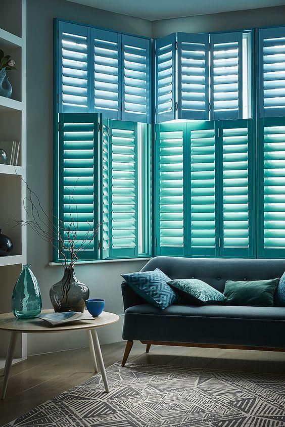 finestre a bovindo con persiane blu piantagione è un'idea chic e audace per una casa costiera o sulla spiaggia