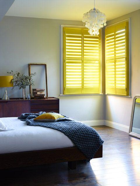 una camera da letto neutra con mobili riccamente colorati e tocchi di giallo brillante: cuscini, lampade e persiane