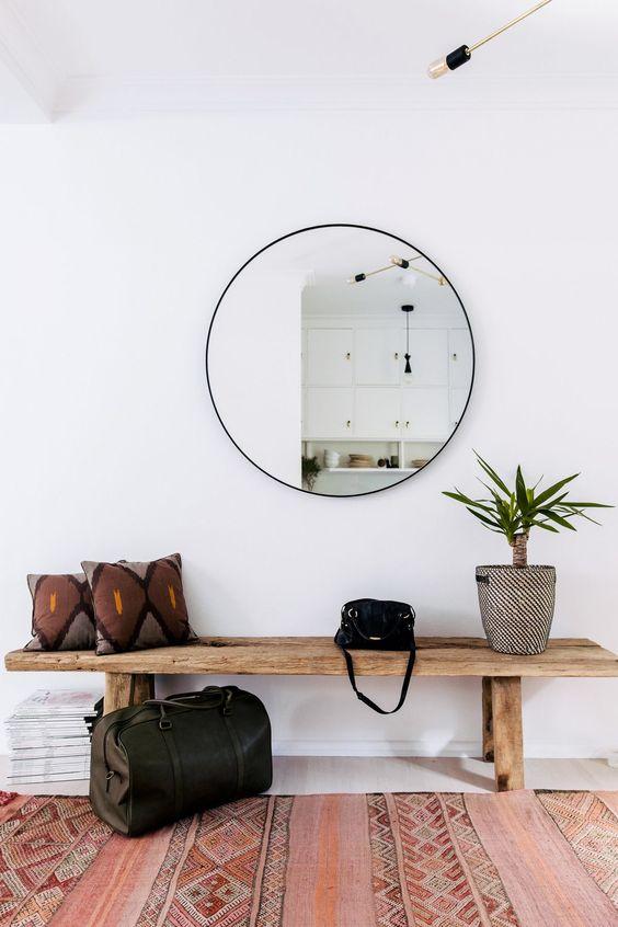 uno specchio rotondo è una decorazione alla moda e un pezzo che raddoppia la luce che arriva all'ingresso