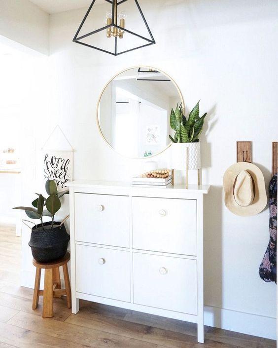 un lampadario con cornice geometrica con tocchi in ottone aggiunge eleganza all'ingresso illuminandolo