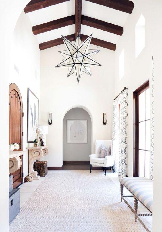un ingresso neutro e luminoso con un lampadario a forma di stella di grandi dimensioni per una dichiarazione