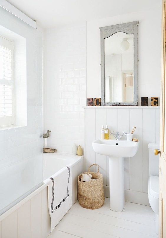 un bagno neutro e carino con un tocco nordico, un cestino per la conservazione, uno specchio vintage e piastrelle bianche