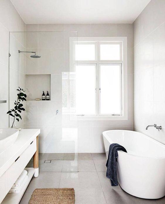 un rinfrescante bagno scandinavo con pareti bianche, una vasca ovale, un lungo lavabo bianco e un tappeto di iuta