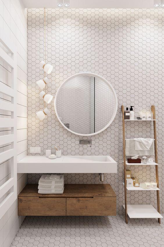 un bagno fresco con piastrelle esagonali bianche e stucco nero, con legno chiaro e lampade a sospensione
