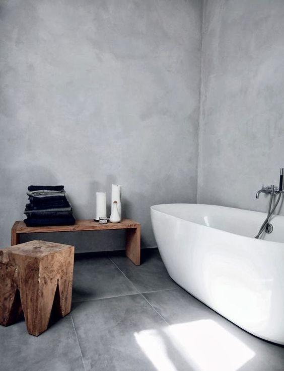 un bagno scandinavo naturale fatto con cemento e piastrelle grigie più sgabelli in legno e una panca