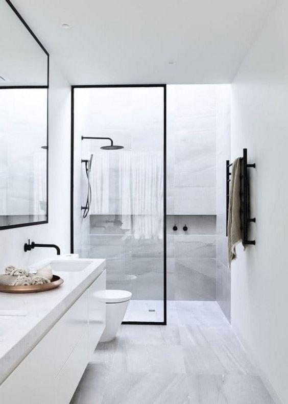 un sereno bagno nordico con piastrelle di marmo grigio, una lunga vanità e tocchi di nero