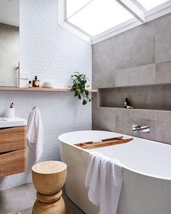 un tranquillo bagno scandinavo con piastrelle grigie, un muro bianco, molto legno naturale nell'arredamento e un lucernario