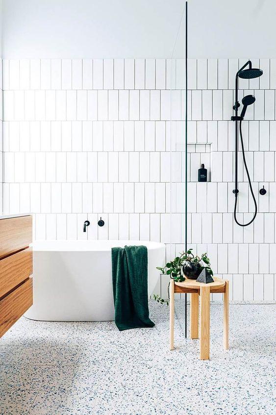un tranquillo bagno scandinavo con pavimento maculato, piastrelle bianche con stucco nero e mobili in legno
