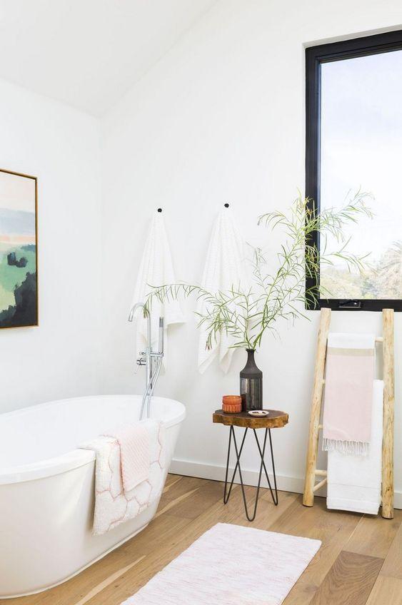 un sereno bagno scandinavo con una vasca ovale, uno sgabello in legno con gambe a forcina e una finestra con cornice blakc