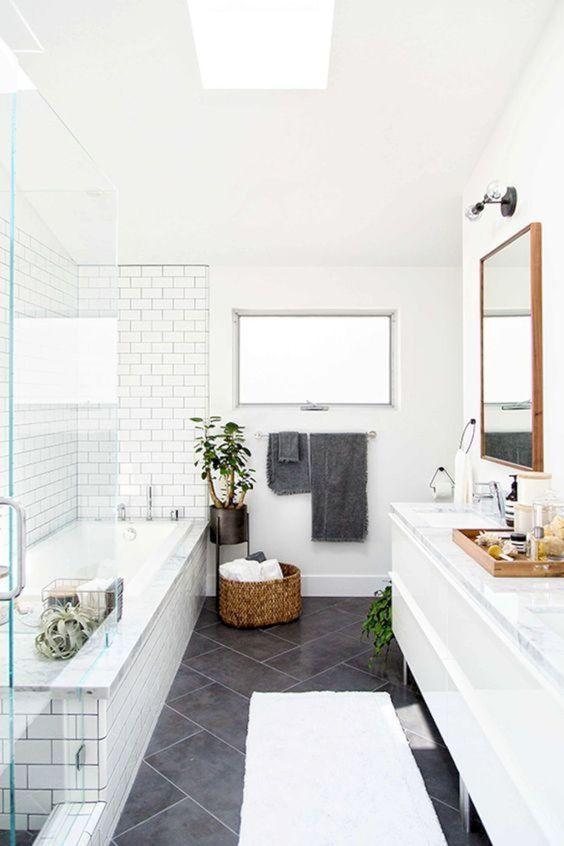 un bagno scandinavo con piastrelle bianche e grigie, un cestino per la conservazione e piante in vaso