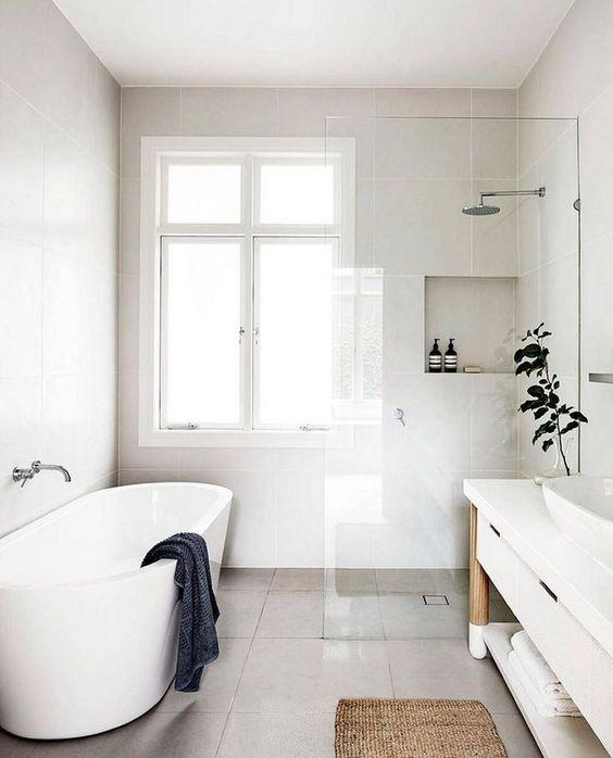 un sereno bagno nordico con vasca ovale, nicchie portaoggetti, un lungo lavabo con lavandino e vegetazione in vaso