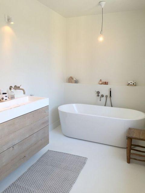 un sereno bagno nordico bianco con una vasca ovale, un lavabo in legno e un tappeto accogliente