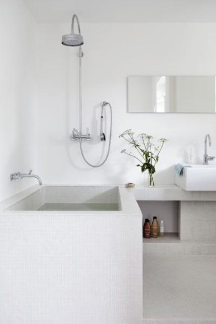 un bagno scandinavo minimalista in bianco e bianco sporco con vasca rivestita di piastrelle e nicchie per riporre gli oggetti