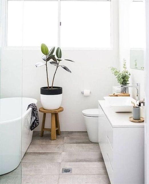 un piccolo bagno nordico con un pavimento in tiile di legno, un lavabo bianco, una vasca ovale e piante in vaso
