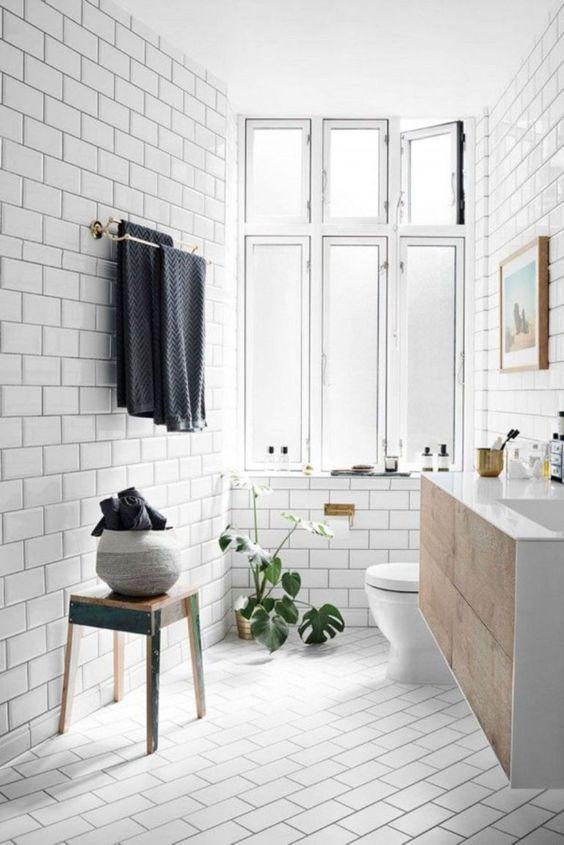 un accogliente bagno Scandi con tocchi vintage, un lavabo in legno =, asciugamani e una grande finestra per la luce naturale